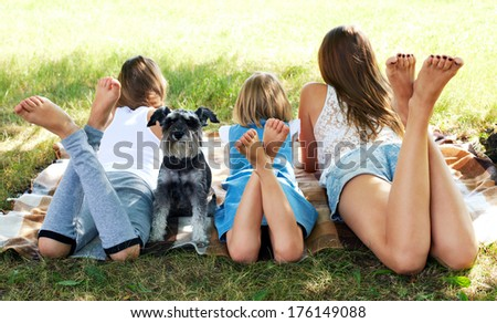 girl lying on the grass with a dog - stock photo