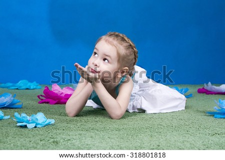 Girl lying on the green carpet with paper flowers - stock photo