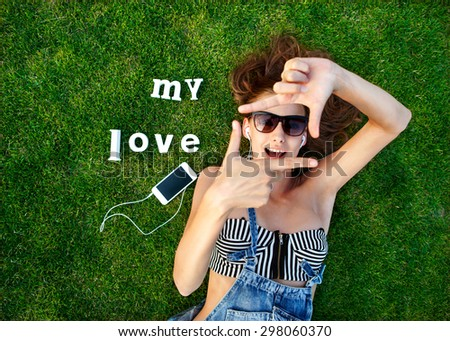 girl lying on the green grass, makes a stop frame arms, listening to music on a white label trave- My Love - stock photo