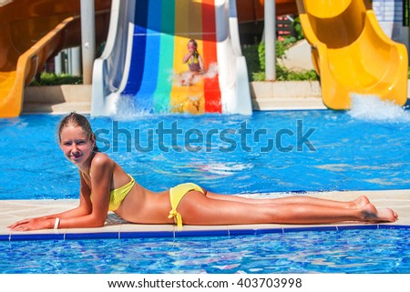 girl lying on the side of the pool. Second child riding a water slide.