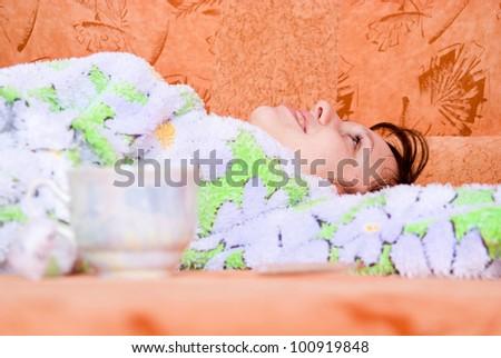 girl lying on the sofa with a mug - stock photo