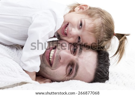 Girl lying on top of her father and they hug and smile - stock photo