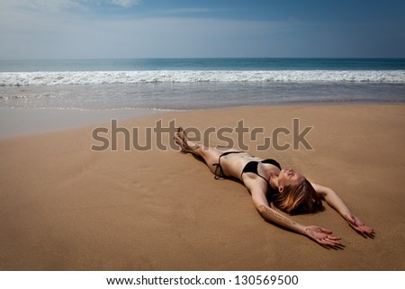 Girl lying on tropical beach, while sunbathing - stock photo