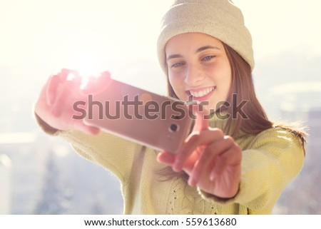 Girl makes a selfie with winter. Cheerful girl making selfie in snow forest background