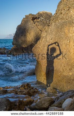 Girl makes heart shape shadow on a rock at the beach