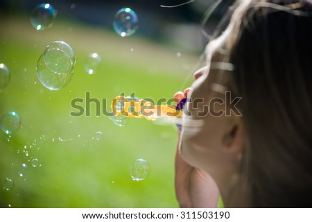 girl makes soap bubble on meadow
