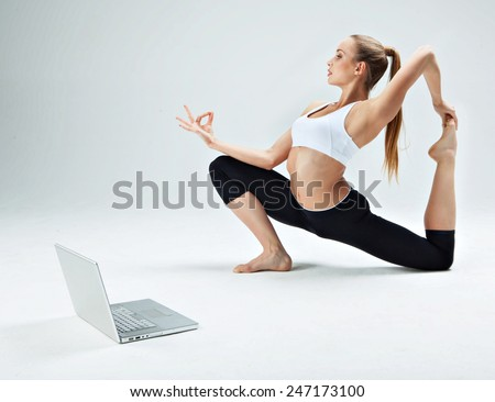 Girl makes yoga exercise online with laptop on the white background - stock photo