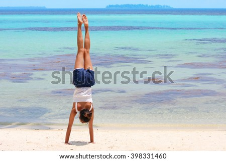 Girl making gymnastics on tropical lagoon beach