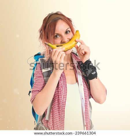 Girl making happy gesture with banan over isolated ocher background