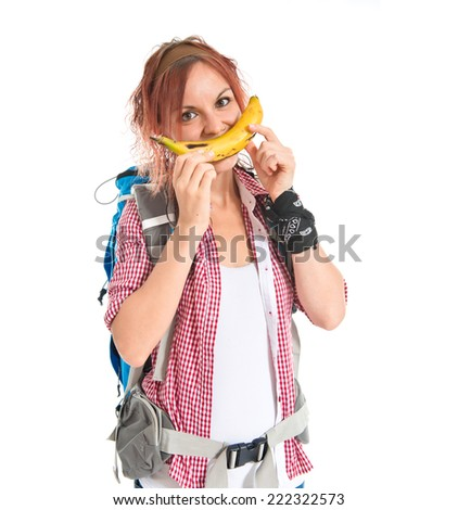 Girl making happy gesture with banana over isolated white background