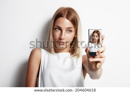 girl making selfie with a mobile phone, focus on the phone - stock photo