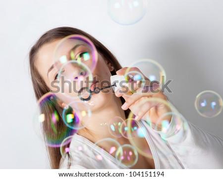Girl making soap bubbles in studio - stock photo