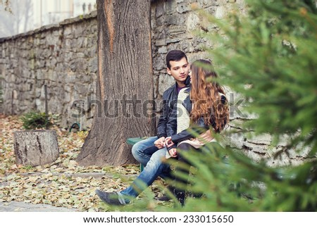 girl man couple sitting autumn park romance - stock photo