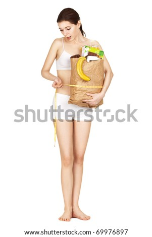 Girl measuring her waist keeping products isolated on a white background,  disappointed with the result