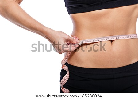 Girl measuring waist circumference after a grueling workout, isolated on white background - stock photo