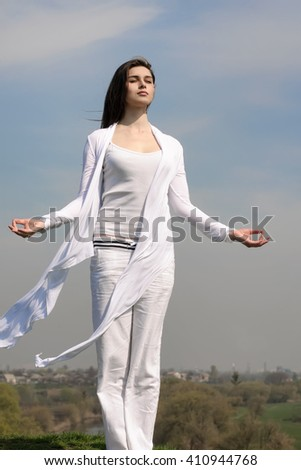 Girl meditates on a hill against the blue sky. She stands her arms to the side and her hair fluttering in the wind. She is wearing in a white loose-fitting clothing. Concept: freedom, health - stock photo
