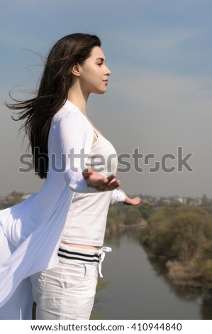 Girl meditates on a hill against the blue sky. She stands her arms to the side and her hair fluttering in the wind.  Concept: freedom, health, cleanliness. - stock photo