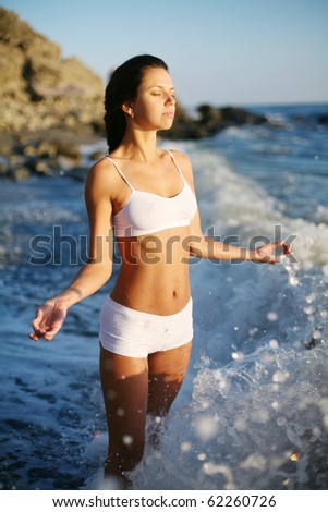 girl meditates standing in the surf.