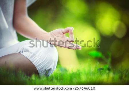 Girl meditating in the park - stock photo