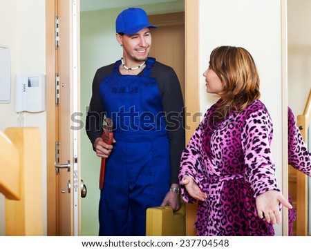Girl meeting plumber at the door at home - stock photo