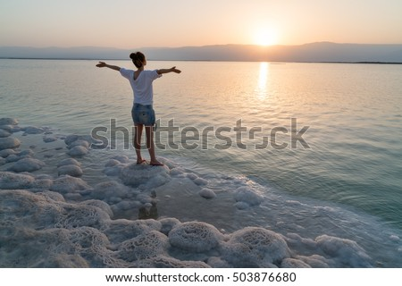 Girl meets sunrise on the shore the Dead Sea in Israel