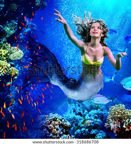 Girl mermaid dive underwater through coral fishes. - stock photo