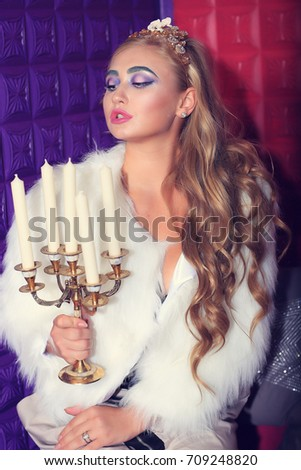 Girl model in a white fur coat sits with candles