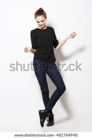 Girl model poses in the studio full-length. Natural, positive, posture.