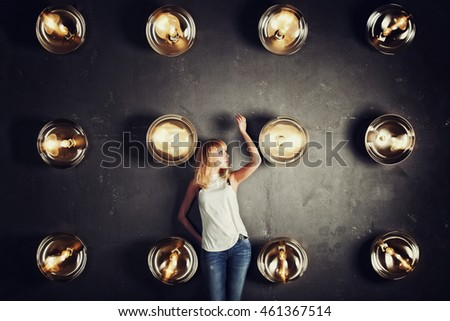 Girl model standing against the wall with spotlights in photo studio