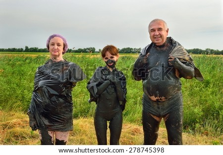 Girl, mom and dad in the therapeutic mud - stock photo