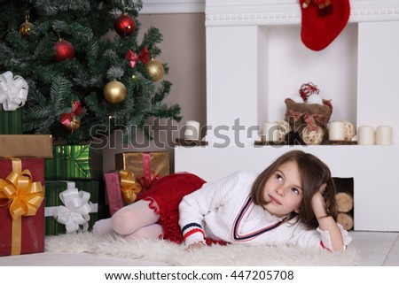 Girl near Christmas tree with presents. A child on Christmas Eve. Happy New Year. - stock photo