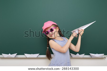 Girl near the school board with paper plane boat - stock photo