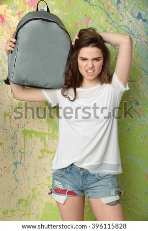 Girl near the wall studio with a backpack on his shoulder - stock photo
