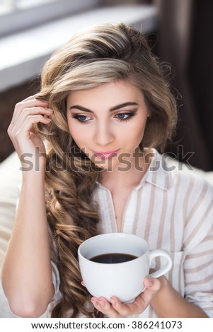 Girl near the window on the sofa drinking coffee from a white mug, coffee with sugar, blonde girl in a white shirt, morning