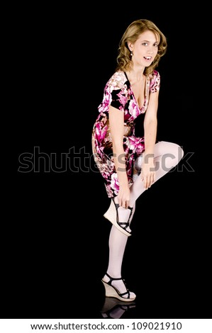 Girl-next-door beauty in colorful spring outfit unbuckling her shoe.
