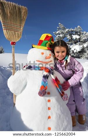 Girl next to snowman - stock photo