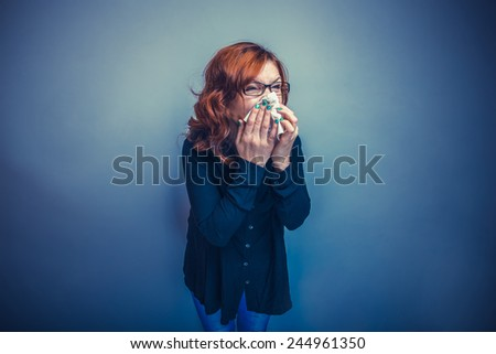 girl of European appearance redheaded blowing his nose into a handkerchief on a gray background cross process - stock photo