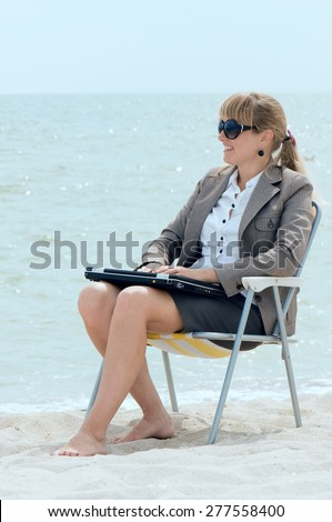 girl of the businesswoman sits in a beach chair on the seashore with the closed laptop and looks afar - stock photo