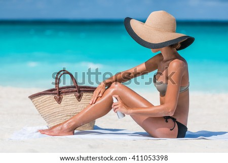 Girl oil spray tanning her legs protection from the sun's uv rays putting sunscreen lotion sunblock Unrecognizable girl with her beach essentials for a summer holiday - straw sun hat and tote bag. - stock photo
