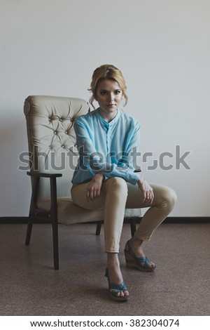 Girl on a beige chair.
