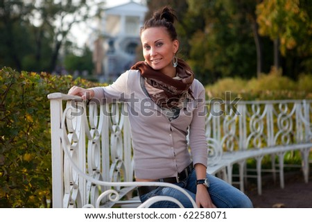 Girl on a bench in the autumn park - stock photo