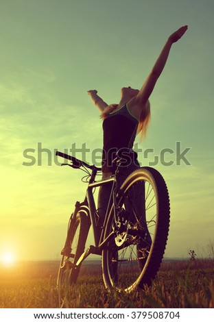 Girl on a bicycle in the sunset - stock photo