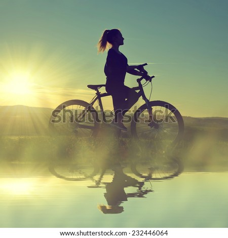 Girl on a bicycle in the sunset reflected on the water surface - stock photo