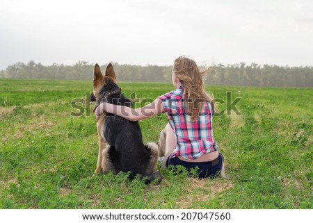 girl on a chair in a field with a clipboard in hand and a German Shepherd
