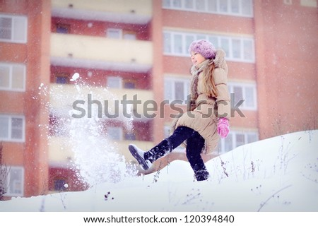 Girl on a high mountain. Lots of snow and cold. Portrait of a child in the winter. Throws snow foot. In the background, a large house. - stock photo