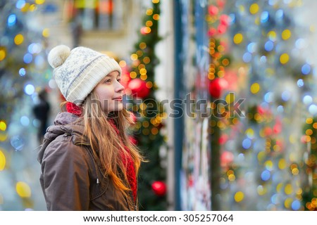 Girl on a Parisian street or at Christmas market looking at shop windows decorated for Christmas - stock photo