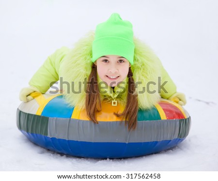 Girl on a Snow Tube Winter Activity - stock photo