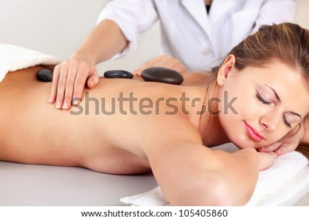 Girl on a stone therapy, hot stone massage. Isolated on white. - stock photo