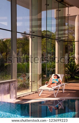 girl on a sun lounger beside the indoor pool