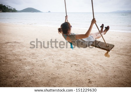 Girl on a swing on a beach - stock photo